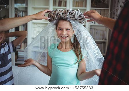 Girl imitating to be an angel by wearing a bubble wrap and an unpacked ring in the new house