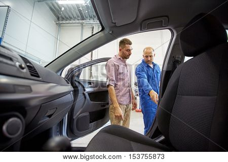 auto service, repair, maintenance and people concept - mechanic and man or owner at car shop