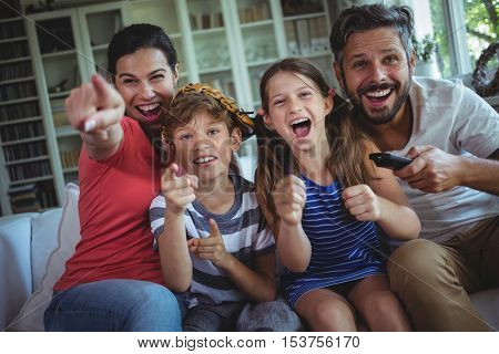 Excited family watching television at home