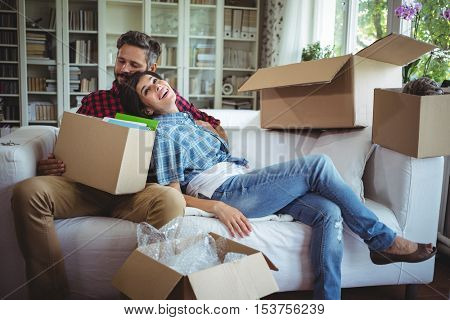 Couple relaxing on sofa while unpacking carton boxes in their new house
