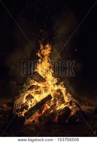 burning logs in the fireplace on black background