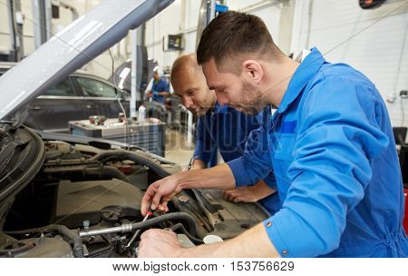 auto service, repair, maintenance and people concept - mechanic men with wrench repairing car at workshop