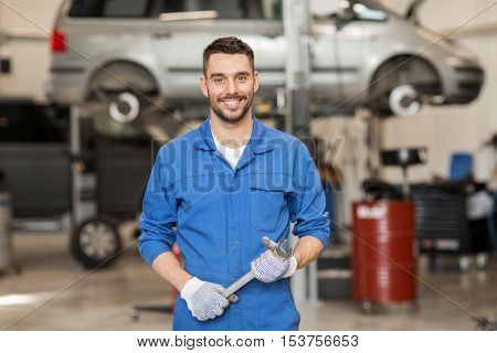 car service, repair, maintenance and people concept - auto mechanic man or smith with wrench at workshop