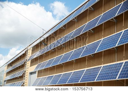 energy sources, power, environment and ecology concept - solar battery panels on building facade