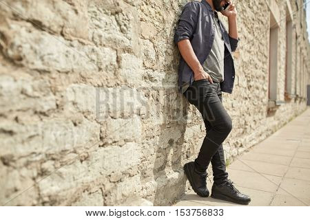 leisure, technology, communication and people concept - close up of man calling and talking on smartphone on street