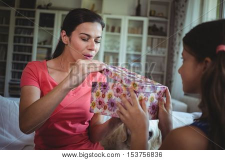 Mother looking at the surprise gift given by her daughter at home