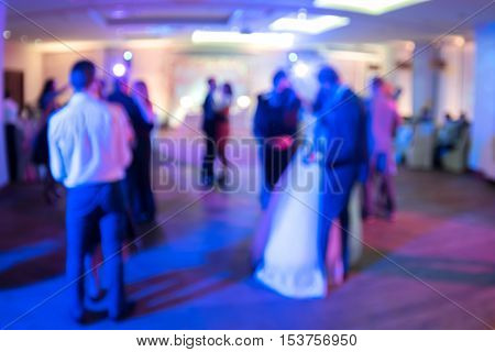 Wedding. Dancing bride and groom couples and guests. Blurred background.