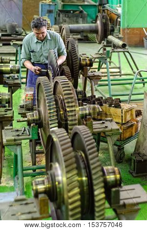 Tyumen, Russia - November 14, 2007: JSC Tyumenskie Motorostroiteli. Plant on production and repair of aviation engines. Mechanic works with part of aviation engine