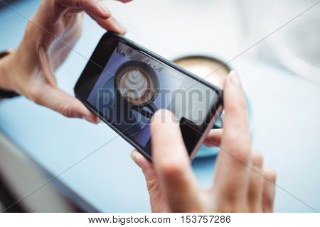 Woman taking photo of a coffee from mobile phone in office