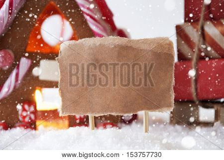 Gingerbread House In Snowy Scenery As Christmas Decoration. Sleigh With Christmas Gifts Or Presents And Snowflakes. Label With Copy Space For Advertisement