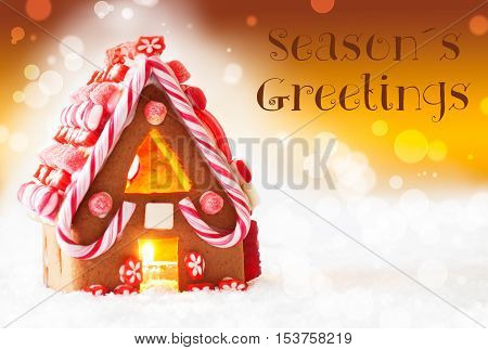 Gingerbread House In Snowy Scenery As Christmas Decoration. Candlelight For Romantic Atmosphere. Golden Background With Bokeh Effect. English Text Seasons Greetings