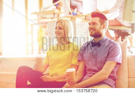 business, startup, people and communication concept - happy man and woman drinking coffee in office