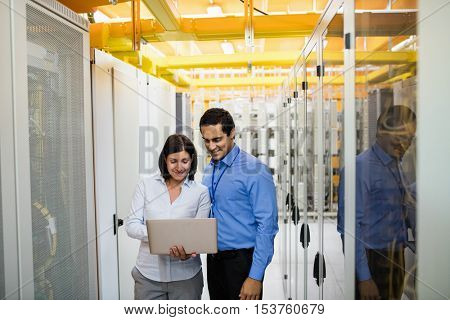 Technicians discussing over laptop in server room
