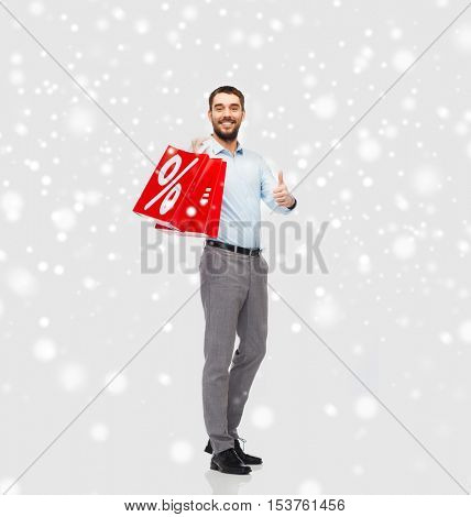 people, sale, christmas, winter and holidays concept - smiling man holding red shopping bags with percentage sign showing thumbs up over snow background