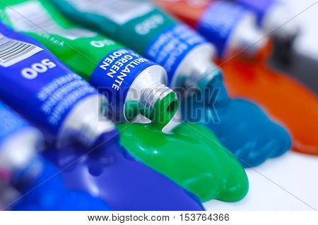 Paint Tubes made out of Tin in Various Colors Squeezed on White Paper Background. Image is composed for design purposes like cards, brochures, magazines, websites