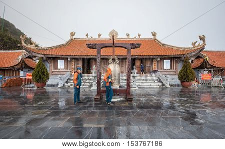 Sa Pa Vietnam - September 18 2016: Temple on top of Fansipan Legend mountain on cloudy with rain staff ringing golden bell before sunset.