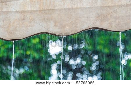 Close focus on rain flowing down from brown canvas roof. Outside is raining on blurry green tree background.