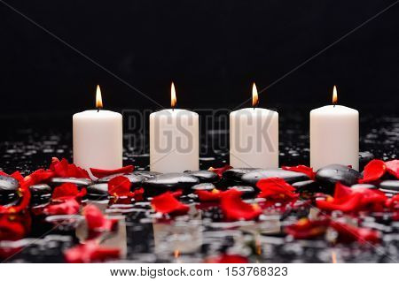 Many rose petals with four candle and therapy stones