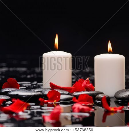 Many rose petals with two candle and therapy stones