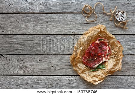 Raw beef steak in craft paper, food background. Top view with copy space on gray rustic wood. Fresh juicy meat, rosemary and herbs. Cooking ingredients, butcher's and grocery concept