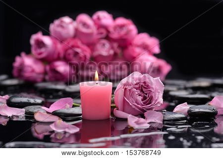 Lying down branch pink rose with candle and therapy stones
