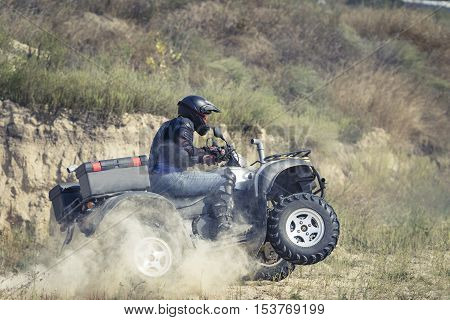 A man riding ATV in sand in protective clothing and a helmet.