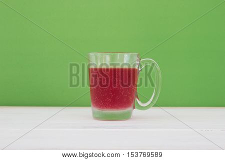 A glass of cool red soft drinks on wooden floor background