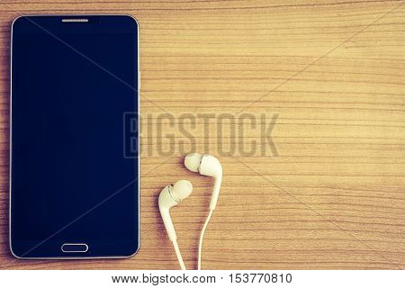 Smartphone with blank screen and in-ear earphones on wooden table