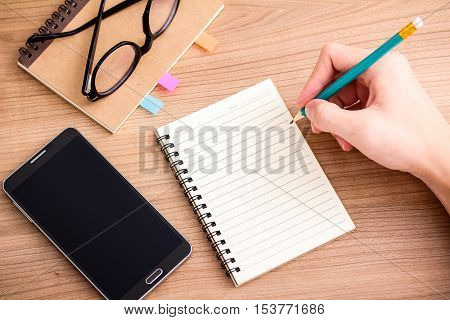 Top view of right hand writing in blank notebook on wooded table with smartphone and glasses