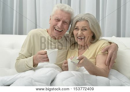 Senior couple resting in bed with cups