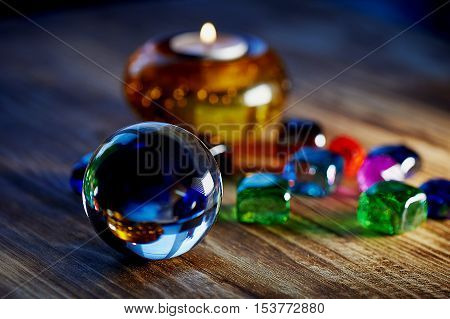 Mysterious cozy glass ball, multi-colored beads, and a candle in a candlestick. Intimacy