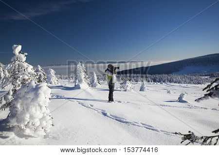 Man photographing magic landscape in winter the mountains