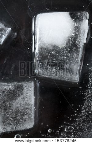 Black frozen water surface with ice cubes