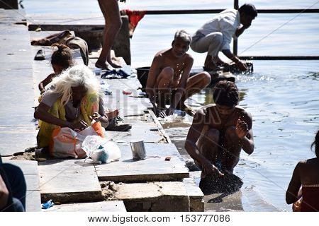 UDAIPUR, RAJASTHAN, INDIA - FEBRUARY 07, 2016 - Unidentified indian people washing their clothes in the water of lake Pichola