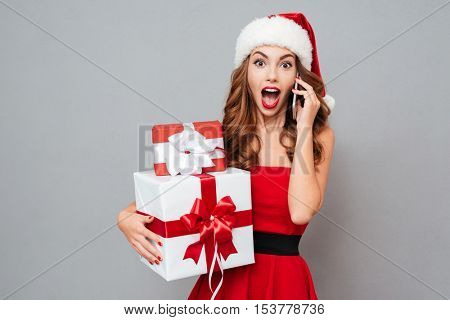 Surprised woman with gifts talks on phone. Santa's helper. Dress and Santa's hat