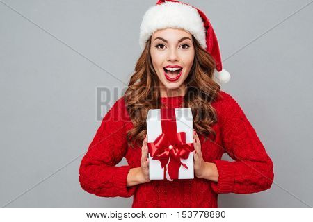 Happy excited young woman in santa claus hat with gift box over gray background