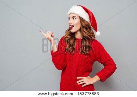 Cheerful lovely young woman in santa claus hat standing and pointing away over gray background