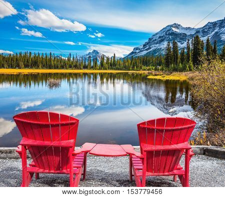 The beautiful nature in northern Rocky Mountains of Canada. Two red comfortable deck chairs on the lake