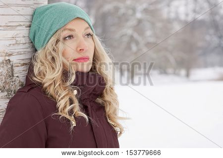 woman leaning against birch tree in snow covered winter landscape gazing into distance