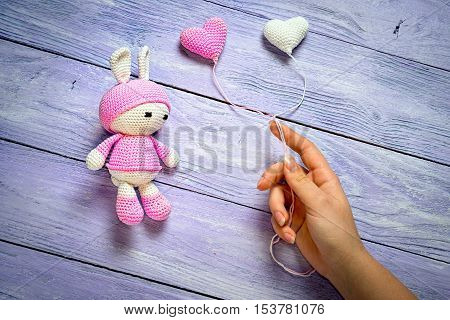 Crocheted Toy Bunny And Hand, Giving Him The Balloons In The Form Of Hearts On Wooden Background As