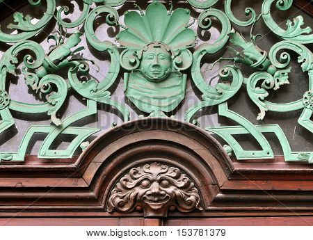 Prague, Czech Republic - April 11, 2016: Detail of the entrance to the old building in Prague. Vintage decorations over the door based on curves shapes and stylized faces.