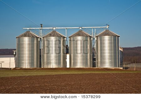 beautiful landscape with silo and field with blue sky