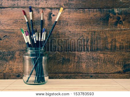 Used paint brush in jar with wooden background