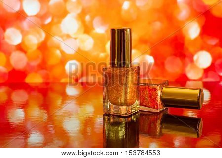 Two nail polish bottles on bright blurred red background with reflection. With copy space