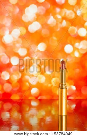Red lipstick on red blurred background with reflection. Copy space included