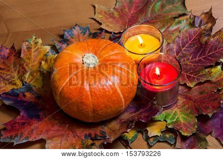 Pumpkin and two lighting candles. Selective focus