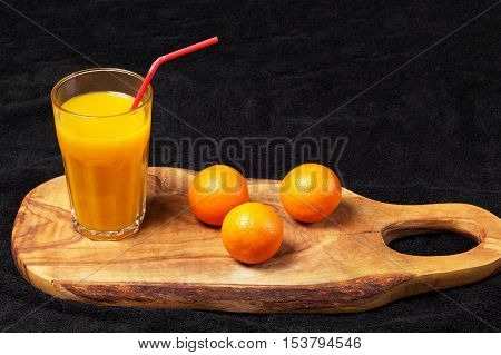 several mature citrus and a glass of juice on a wooden table on a blackboard - mandarins