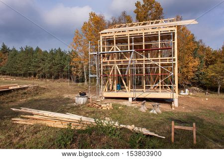 Metal scaffolding around the unfinished house. Construction of ecological house. Wooden frame of house under construction.Framed New Construction of a House. Timber house in building process