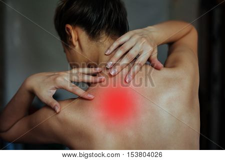 Body pain. Studio shot of beautiful young woman with dark brown hair. Woman suffering from neck ache. Healthy lifestyle. Back and spine disease. back view tired female. neck colored red