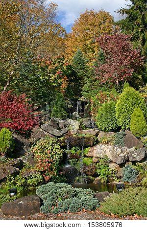 a cascade tumbles over rocks amid fall foliage and splashes into a small pond.